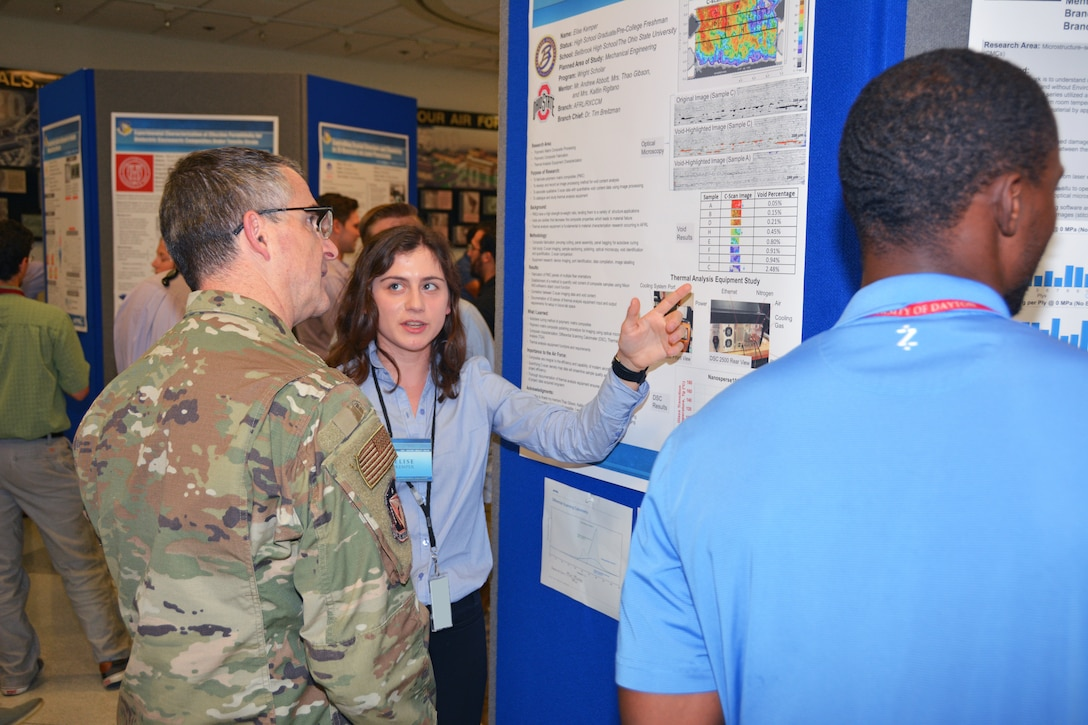 Elise Kemper, a 2019 Belbrook High School graduate, presents her research poster to Maj. Gen. William T. Cooley, commander of the Air Force Research Laboratory, at the summer student research poster session Aug. 1. Kemper's research area this summer was Polymeric Matrix Composites. She will be attending Ohio State University this fall, studying mechanical engineering. (U.S. Air Force photo/Spencer Deer)