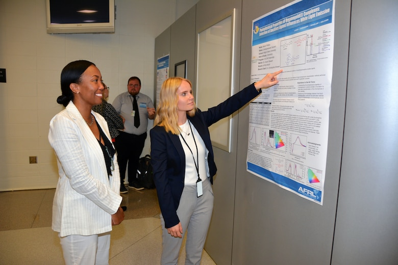 Alexis Phillips, an undergraduate student at Wright State University, presents her poster on Photophysical Properties of Organogold(I) Complexes: Selection of Ancillary Ligand Influences White Light Emission, to Asheley Blackford, who is in her fourth year of managing the student researcher poster session for AFRL's Materials and Manufacturing Directorate. (U.S. Air Force photo/Spencer Deer)