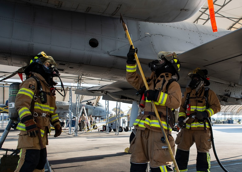 Firefighters from the 23d Civil Engineer Squadron (CES) attempt to open an engine panel during an A-10C Thunderbolt II egress training scenario, Aug. 9, 2019, at Moody Air Force Base, Ga. The 23d CES conducted the exercise to test their capability in extinguishing an A-10 on fire while simultaneously rescuing its pilot. The training also served as an opportunity for firefighter crew chiefs and their Airmen to increase team cohesion. (U.S. Air Force photo by Airman Azaria E. Foster)