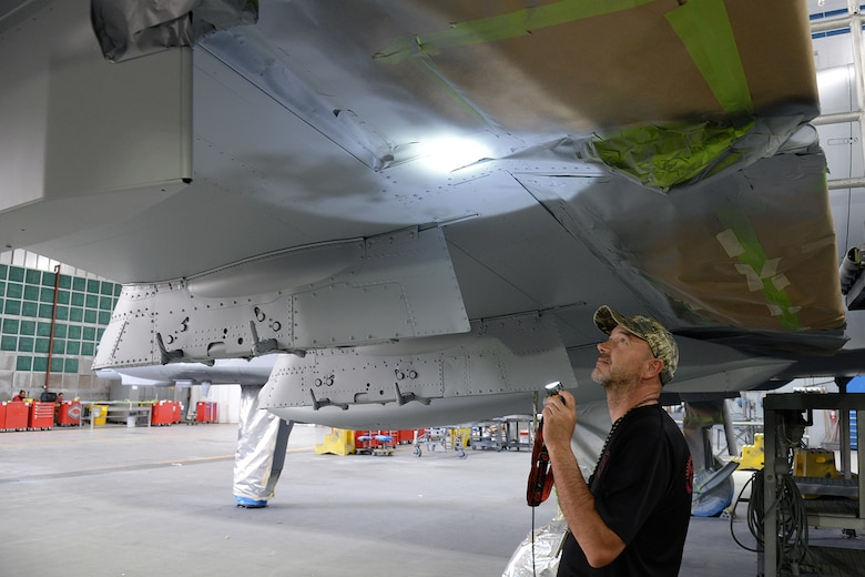 576th Aircraft Maintenance Squadron corrosion control painter Dale Benoit inspects newly applied paint on the underside of the new wing of an A-10 Thunderbolt II, tail no. 80-0252, at Hill Air Force Base, Utah, July 3, 2019. The aircraft was the last of 173 A-10s to receive new wings under the Enhanced Wing Assembly program to extend the flying service life of the fleet.  (U.S. Air Force photo by Alex R. Lloyd)