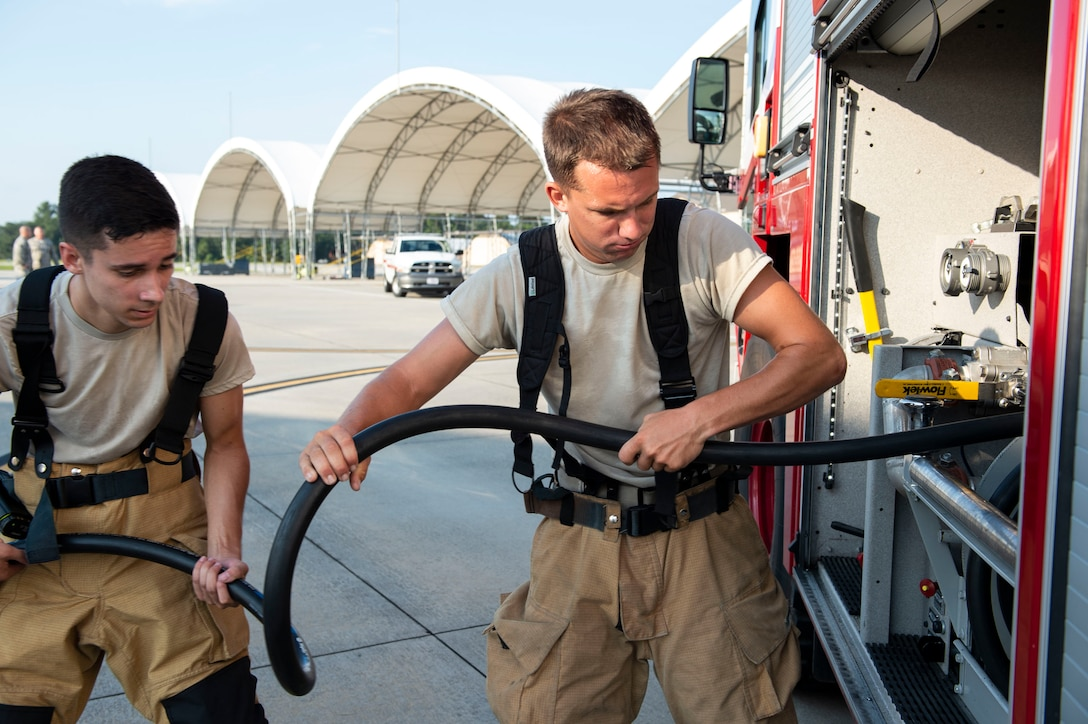 Senior Airman Tyler Goshe, left, and Airman 1st Class Zachary Mabee, both 23d Civil Engineer Squadron (CES) firefighters, wrap a hose after completing an A-10C Thunderbolt II egress training scenario, Aug. 9, 2019, at Moody Air Force Base, Ga The 23d CES conducted the exercise to test their capability in extinguishing an A-10 on fire while simultaneously rescuing its pilot. The training also served as an opportunity for firefighter crew chiefs and their Airmen to increase team cohesion. (U.S. Air Force photo by Airman Azaria E. Foster)