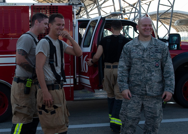 Firefighters from the 23d Civil Engineer Squadron (CES) share a laugh after completing an A-10C Thunderbolt II egress training scenario, Aug. 9, 2019, at Moody Air Force Base, Ga. The 23d CES conducted the exercise to test their capability in extinguishing an A-10 on fire while simultaneously rescuing its pilot. The training also served as an opportunity for firefighter crew chiefs and their Airmen to increase team cohesion. (U.S. Air Force photo by Airman Azaria E. Foster)