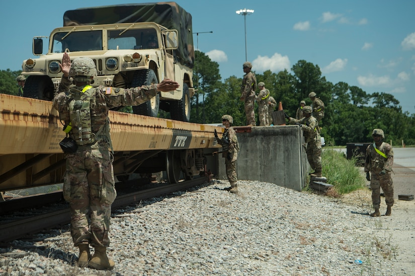 U.S. Army Soldiers from Fort Bragg, N.C., direct a High Mobility Multipurpose Wheeled Vehicle onto a rail system during Exercise Dragon Lifeline Aug. 7, 2019, at Joint Base Charleston's Naval Weapons Station, S.C. The deployment readiness exercise combined the capabilities of service members from Fort Bragg, N.C., Joint Base Charleston, S.C., and Joint Base Langley-Eustis, Va., and focused on the rapid deployment of equipment, vehicles and personnel. Participants shared knowledge and tested their efficiency in moving assets by air, land, rail and sea during the training event. The annual exercise is just one of the critical readiness exercises the DOD conducts to maintain a lethal and ready force. (U.S. Air Force photo by Tech. Sgt. Christopher Hubenthal)
