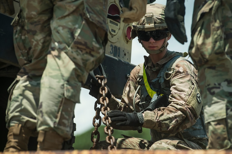U.S. Army Spc. Lexie West, a wheeled vehicle mechanic assigned to the 659th Support Maintenance Company, 264th Combat Sustainment Support Battalion from Fort Bragg, N.C., secures a military vehicle onto a rail system during Exercise Dragon Lifeline Aug. 7, 2019, at Joint Base Charleston's Naval Weapons Station, S.C. The deployment readiness exercise combined the capabilities of service members from Fort Bragg, N.C., Joint Base Charleston, S.C., and Joint Base Langley-Eustis, Va., and focused on the rapid deployment of equipment, vehicles and personnel. Participants shared knowledge and tested their efficiency in moving assets by air, land, rail and sea during the training event. The annual exercise is just one of the critical readiness exercises the DOD conducts to maintain a lethal and ready force. (U.S. Air Force photo by Tech. Sgt. Christopher Hubenthal)