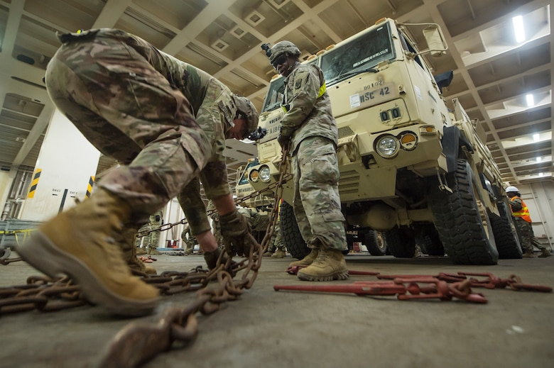 U.S. Army Spc. Robert Smedley, left, and U.S. Army Staff Sgt. Conrad Stewart, both assigned to the 18th Field Artillery Brigade, 188th Brigade Support Battalion from Fort Bragg, N.C., secure a military vehicle onto the Logistics Naval Vessel Cape Decision during Exercise Dragon Lifeline Aug. 7, 2019, at the Federal Law enforcement Training Center in Charleston, S.C. The exercise provided military personnel with experience needed to support rapid deployment operations across air, land, rail and sea. JB Charleston helps to provide rapid global deployment of personnel and equipment to deployed locations across the globe. The annual exercise is just one of the critical readiness exercises the DOD conducts to maintain a lethal and ready force. (U.S. Air Force photo by Tech. Sgt. Christopher Hubenthal)