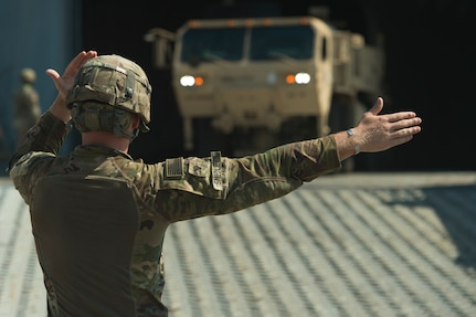 U.S. Army Spc. Robert Smedley, assigned to the 18th Field Artillery Brigade, 188th Brigade Support Battalion from Fort Bragg, N.C., directs military vehicles off Logistics Naval Vessel Cape Decision during Exercise Dragon Lifeline Aug. 7, 2019, at the Federal Law enforcement Training Center, S.C. The deployment readiness exercise combined the capabilities of service members from Fort Bragg, N.C., Joint Base Charleston, S.C., and Joint Base Langley-Eustis, Va., focusing on the rapid deployment of equipment, vehicles and personnel. Participants shared knowledge and tested their efficiency in moving assets by air, land, rail and sea during the training event. The annual exercise is just one of the critical readiness exercises the DOD conducts to maintain a lethal and ready force. (U.S. Air Force photo by Tech. Sgt. Christopher Hubenthal)