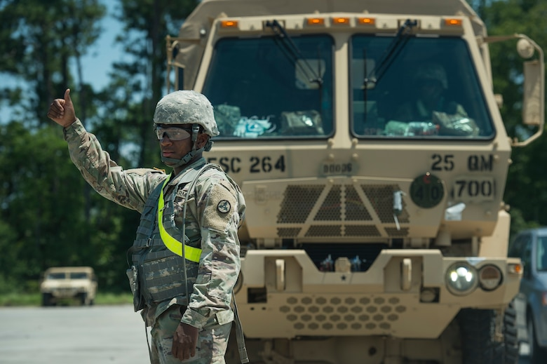 A U.S. Army Soldier signals military vehicles are ready to be onloaded onto a rail system during Exercise Dragon Lifeline Aug. 7, 2019, at Joint Base Charleston's Naval Weapons Station, S.C. The deployment readiness exercise combined the capabilities of service members from Fort Bragg, N.C., Joint Base Charleston, S.C., and Joint Base Langley-Eustis, Va., focused on the rapid deployment of equipment, vehicles and personnel. Participants shared knowledge and tested their efficiency in moving assets by air, land, rail and sea during the training event. The annual exercise is just one of the critical readiness exercises the DOD conducts to maintain a lethal and ready force. (U.S. Air Force photo by Tech. Sgt. Christopher Hubenthal)