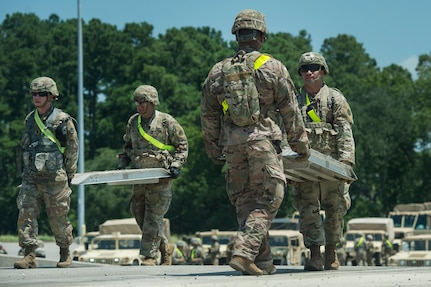 U.S. Army Soldiers from Fort Bragg, N.C., move equipment to prepare a rail system before receiving military vehicles as part of Exercise Dragon Lifeline Aug. 7, 2019, at Joint Base Charleston's Naval Weapons Station, S.C. The exercise provided military personnel with experience needed to support rapid deployment operations across air, land, rail and sea. JB Charleston helps to provide rapid global deployment of personnel and equipment to deployed locations across the globe. The annual exercise is just one of the critical readiness exercises the DOD conducts to maintain a lethal and ready force. (U.S. Air Force photo by Tech. Sgt. Christopher Hubenthal)