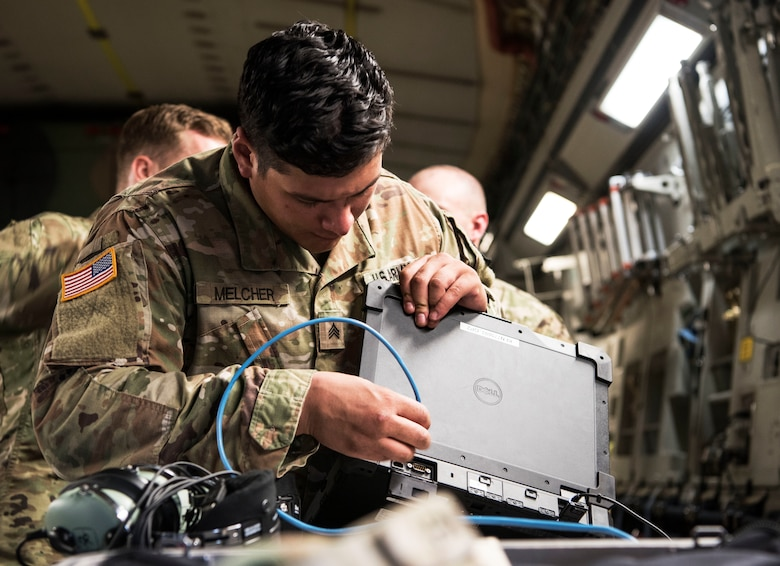 U.S. Army Sgt. Brandon Melcher, a ken operator team chief assigned to the 50th Expeditionary Signal Battalion Enhanced, prepares equipment prior to conducting aerial operations as part of Exercise Dragon Lifeline August 8, 2019, at Joint Base Charleston, S.C. The exercise provided military personnel with experience needed to support rapid deployment operations across air, land, rail and sea. JB Charleston helps to provide rapid global deployment of personnel and equipment to deployed locations across the globe. The annual exercise is just one of the critical readiness exercises the DOD conducts to maintain a lethal and ready force. (U.S. Air Force photo by Staff Sgt. Tenley Long)