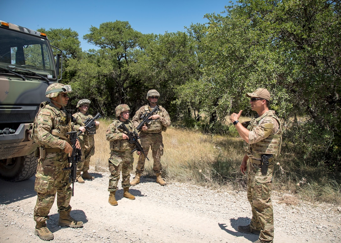 Master Sgt. Joshua Mccaslin, right, 3d Weather Squadron (WS) division Staff Weather Officer, briefs Airmen from the 3d Weather Squadron during a certification field exercise (CFX), July 29, 2019, at Camp Bowie Training Center, Texas. The CFX was designed to evaluate the squadron's overall tactical ability and readiness to provide the U.S. Army with full spectrum environmental support to the Joint Task Force (JTF) fight. The CFX immersed Airmen into all the aspects of what could come with a deployment such as counter improvised explosive device awareness. (U.S. Air Force photo by Airman 1st Class Eugene Oliver)