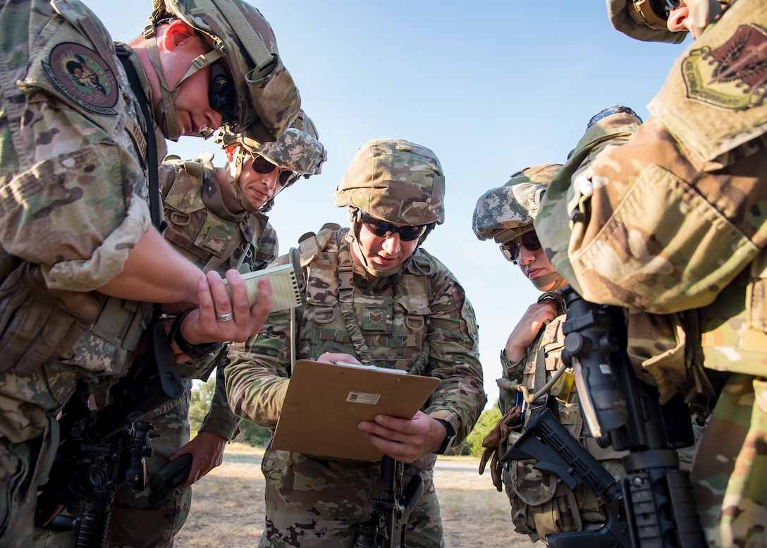 Staff Weather Officers from the 3d Weather Squadron, discuss strategy during a certification field exercise (CFX), July 31, 2019, at Camp Bowie Training Center, Texas. The CFX was designed to evaluate the squadron's overall tactical ability and readiness to provide the U.S. Army with full spectrum environmental support to the Joint Task Force (JTF) fight. The CFX immersed Airmen into all the aspects of what could come with a deployment such as Land Navigation. (U.S. Air Force photo by Airman 1st Class Eugene Oliver)