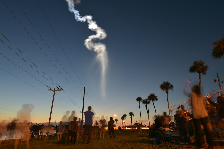 Dozens of people observe an Atlas V rocket Aug. 8, 2019, as it carries the Fifth Advanced Extremely High Frequency satellite toward space after it was launched from Cape Canaveral Air Force Station, Florida. In April, Airmen assigned to Travis Air Force Base, California, transported the satellite to Florida. The satellite will provide enhanced communications for high-priority military assets. (U.S. Air Force photo by Airman 1st Class Dalton Williams)