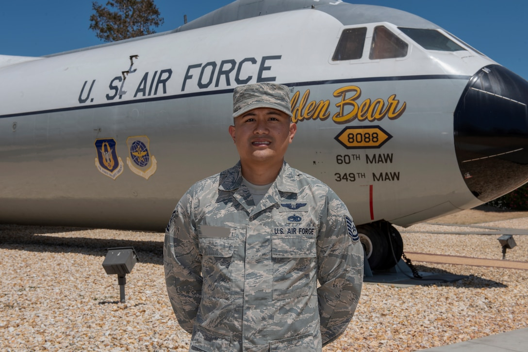 "U.S. Air Force Tech. Sgt. Ron, 860th Aircraft Maintenance Squadron flight line expediter, stands in front of a C-141B Starlifter known as the ""Golden Bear"" July 23, 2019, at Travis Air Force Base, California. Ron completed remote pilot aircraft training July 12 and is one of the few enlisted Airmen the Air Force selected to serve as pilots. This photo has been altered for security purposes by blurring out the last name on the uniform. (U.S. Air Force photo by Tech. Sgt. James Hodgman)"