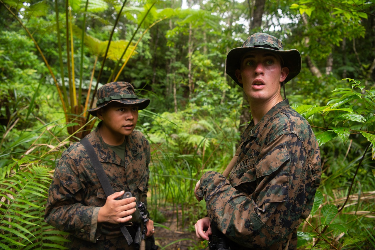 Two Navy service members move through the jungle
