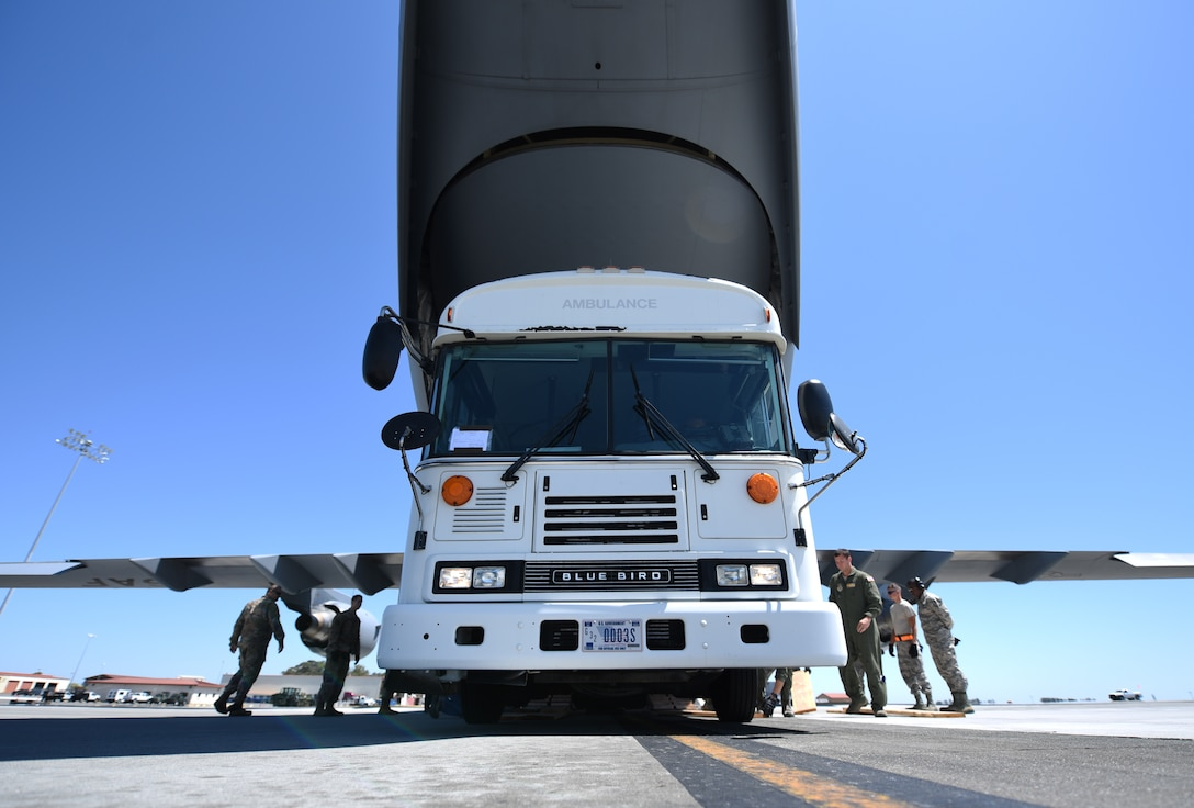 A simulated ambulance is loaded onto a C-17 Globemaster III aircraft Aug. 1, 2019, at Travis Air Force Base, California. The load-up was part of a joint force mobility exercise involving Airmen from Travis AFB and March Air Reserve Base, California. (U.S. Air Force photo by Senior Airman Christian Conrad)