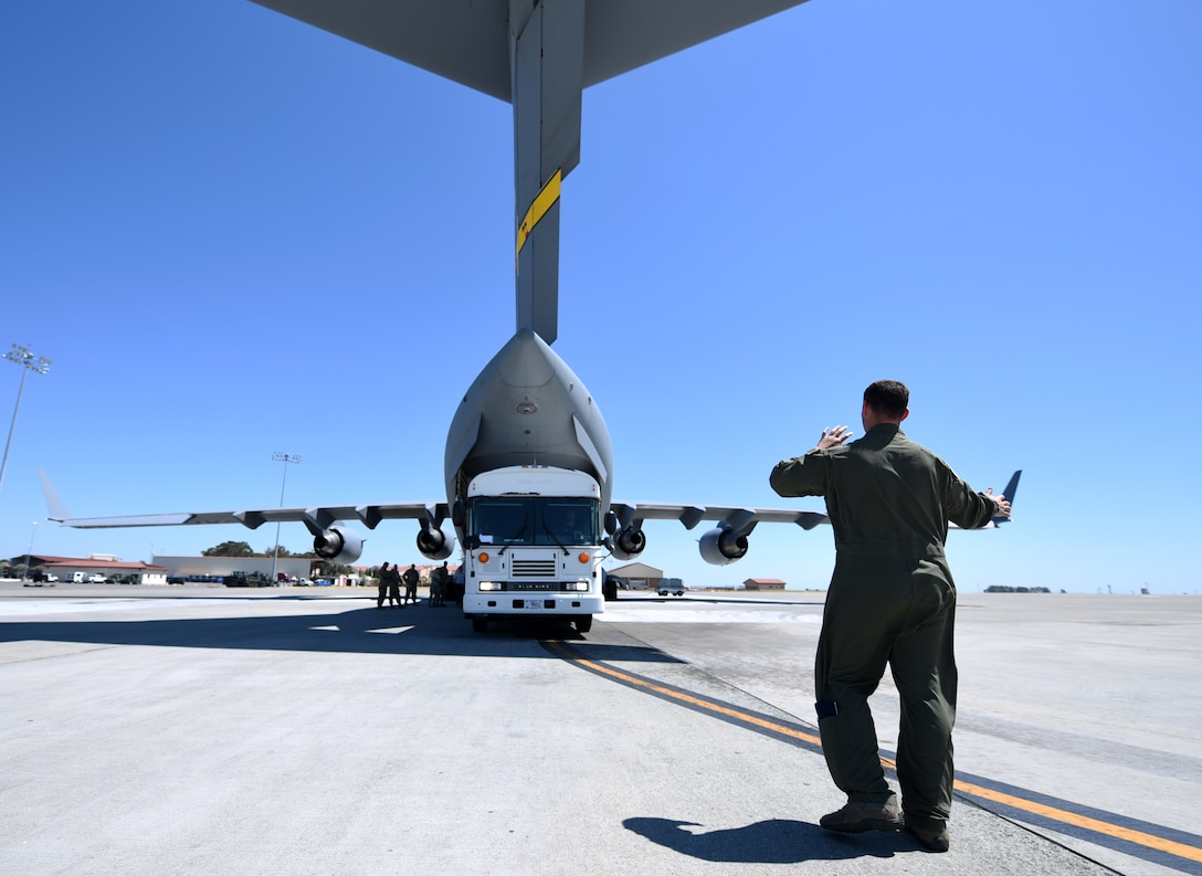 An Airman from March Reserve Base, California, directs the load of a simulated ambulance into a C-17 Globemaster III aircraft Aug. 1, 2019, at Travis Air Force Base, California. The exercise, despite representing a single aspect of the Air Force mobility mission, was an opportunity to encourage joint-force operability between active duty and reserve personnel. (U.S. Air Force photo by Senior Airman Christian Conrad)