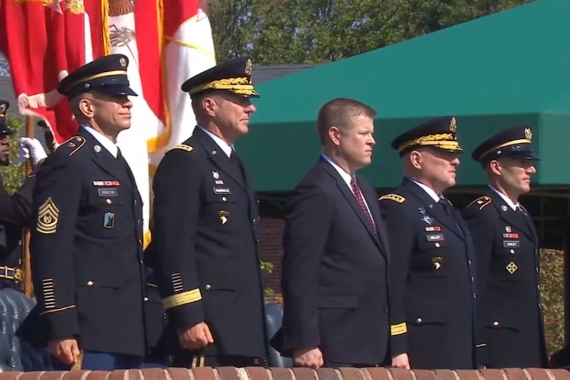 Five men stand shoulder to shoulder during a ceremony.