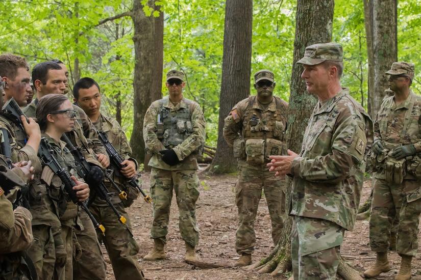 Man speaks to troops in the field.