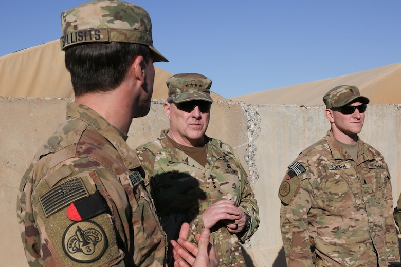 Soldiers speak in desert.
