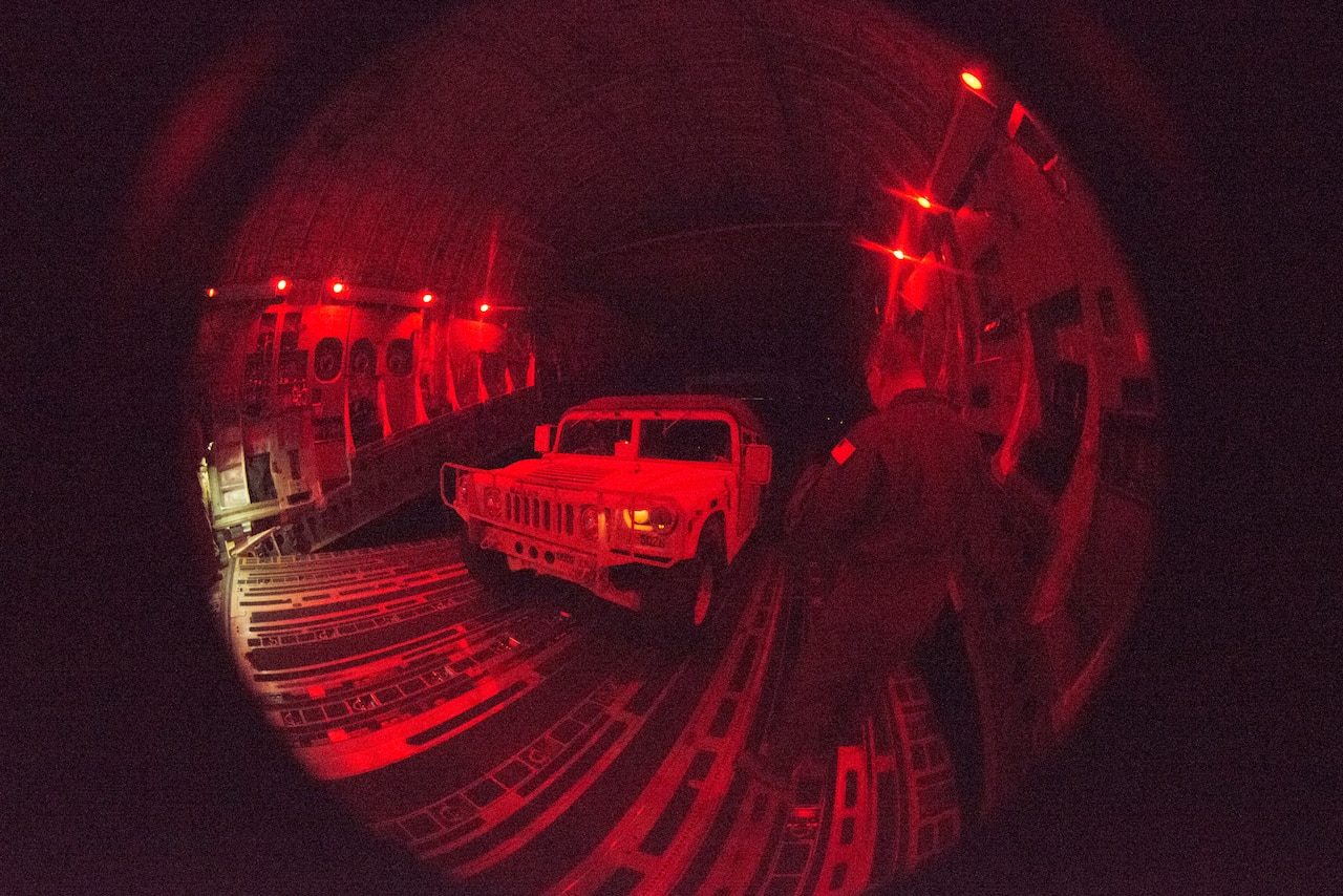 A red-light fisheye image of a tactical truck inside a transport aircraft.