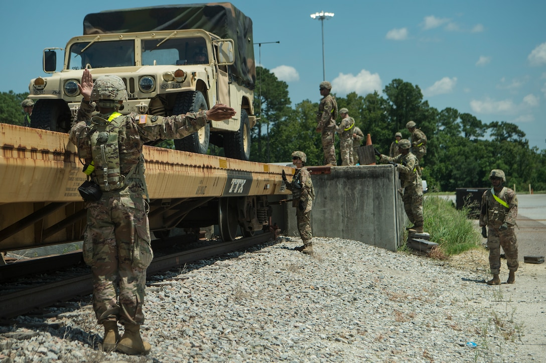 A soldier in camouflage uniform and wearing a helmet uses arm signals to guide a tactical truck onto a yellow flatbed railcar.
