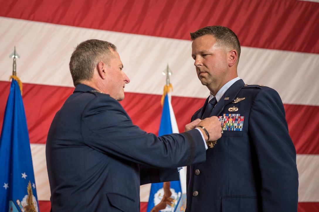"""Lt. Col. John """"J.T."""" Hourigan (right), a pilot for the 123rd Airlift Wing, is pinned with the Distinguished Flying Cross by Gen. David L. Goldfein, Air Force chief of staff, during a ceremony at the Kentucky Air National Guard Base in Louisville, Ky., Aug. 10, 2019. Hourigan earned the award for preventing a catastrophic, in-flight mishap that would have resulted in the loss of aircraft and crew if not for his decisive action. (U.S. Air National Guard photo by Staff Sgt. Joshua Horton)"""