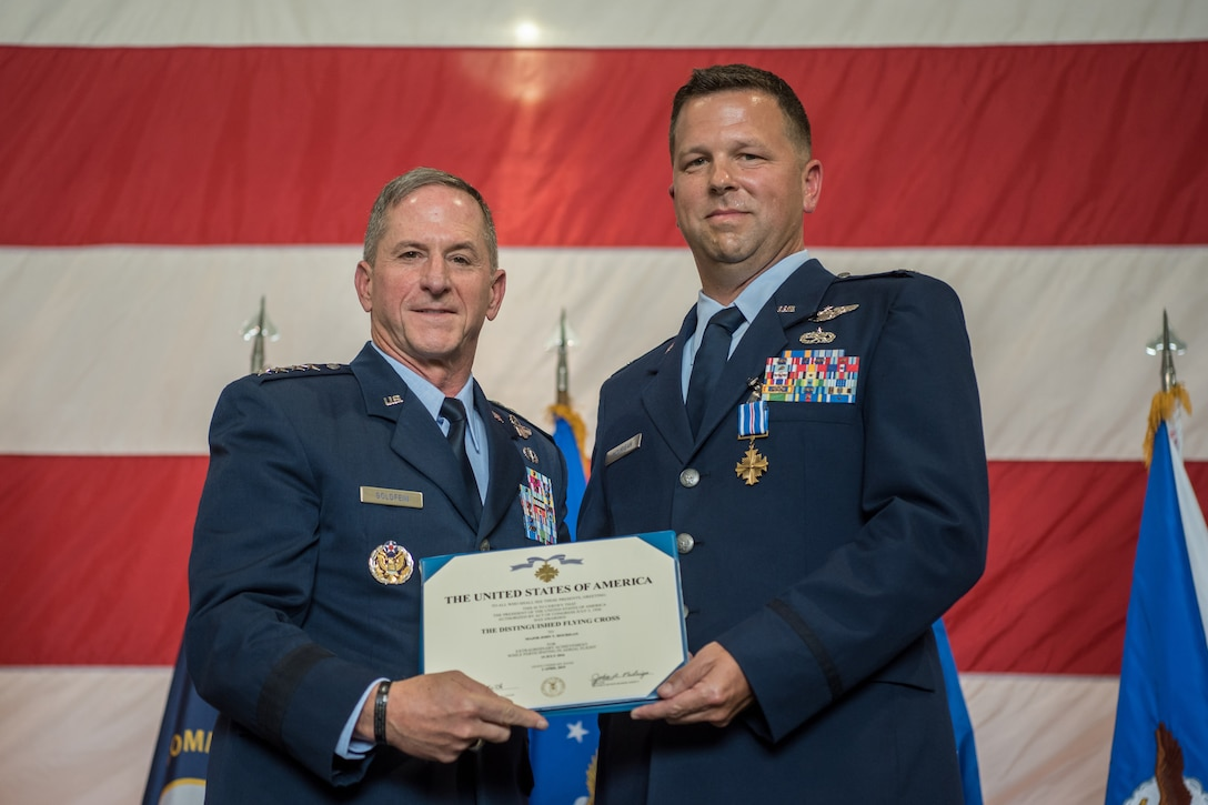 """Lt. Col. John """"J.T."""" Hourigan (right), a pilot for the 123rd Airlift Wing, receives the Distinguished Flying Cross from Gen. David L. Goldfein, Air Force chief of staff, during a ceremony at the Kentucky Air National Guard Base in Louisville, Ky., Aug. 10, 2019. Hourigan earned the award for preventing a catastrophic, in-flight mishap that would have resulted in the loss of aircraft and crew if not for his decisive action. (U.S. Air National Guard photo by Staff Sgt. Joshua Horton)"""