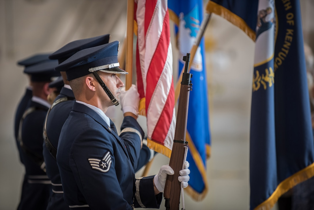 """The 123rd Airlift Wing Honor Guard presents the colors during a ceremony to bestow the Distinguished Flying Cross at the Kentucky Air National Guard Base in Louisville, Ky., Aug. 10, 2019. The award recipient, Lt. Col. John """" J.T."""" Hourigan, earned the medal for decisive action following a catastrophic mechanical failure while flying a C-130 aircraft during a routine training sortie, saving the lives of six crew members and a $30 million aircraft. (U.S. Air National Guard photo by Lt. Col. Dale Greer)"""