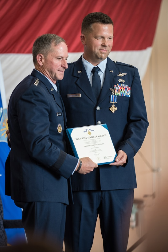 """Air Force Chief of Staff Gen. David L. Goldfein (left) presents the Distinguished Flying Cross to Lt. Col. John """"J.T."""" Hourigan, a pilot in the 123rd Airlift Wing, during a ceremony the Kentucky Air National Guard Base in Louisville, Ky., Aug. 10, 2019. Hourigan earned the medal for decisive action following a catastrophic mechanical failure while flying a C-130 Hercules during a routine training sortie, saving the lives of six crew members and a $30 million aircraft. (U.S. Air National Guard photo by Lt. Col. Dale Greer)"""