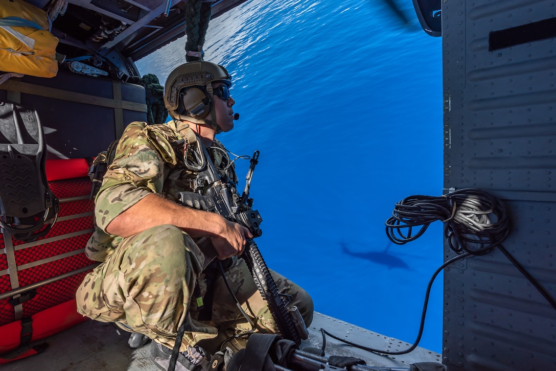 A U.S. Air Force pararescueman assigned to the 31st Rescue Squadron, looks out over the ocean while aboard an HH-60G Pave Hawk, July 26, 2019, out of Kadena Air Base, Japan. The 31st RQS consists of combat rescue officers, pararescue specialists and survival, evasion, resistance and escape specialists who work together to facilitate the return of isolated personnel back to friendly forces. (U.S. Air Force photo by Airman 1st Class Matthew Seefeldt)