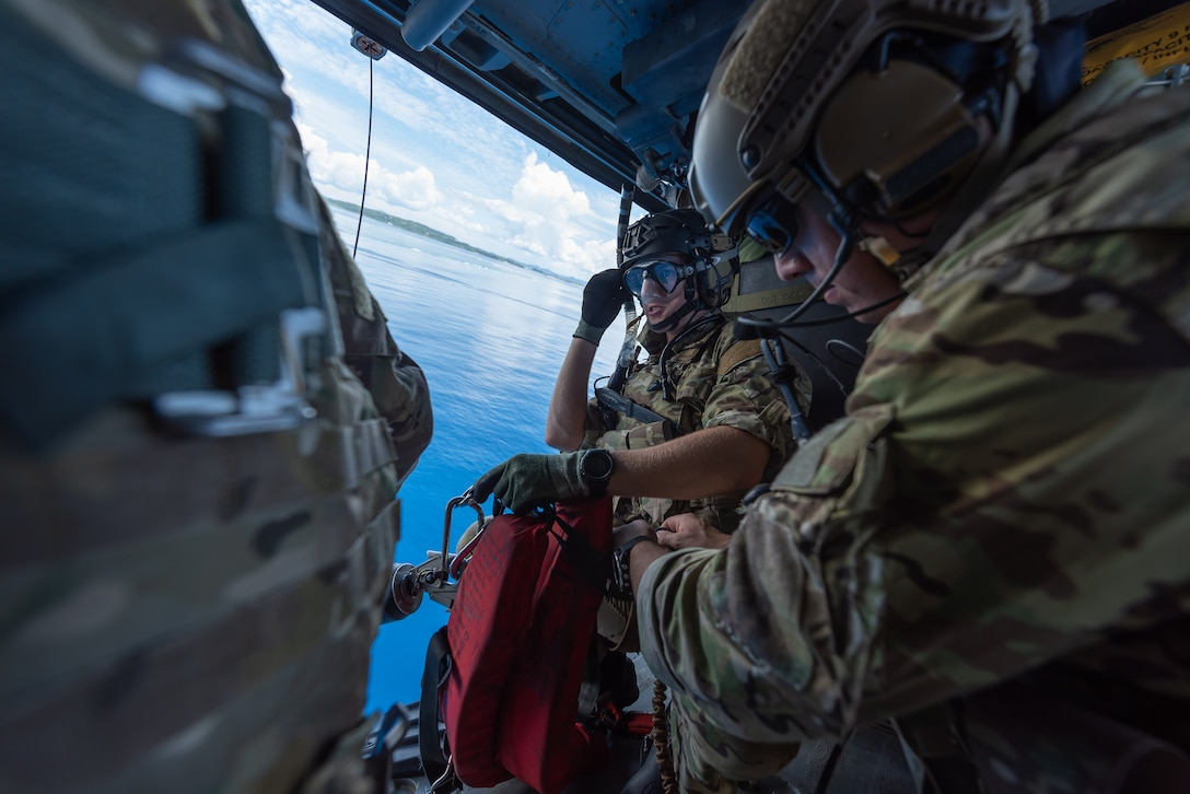 Two U.S. Air Force pararescuemen assigned to the 31st Rescue Squadron, prepare a hoist for a water operation while aboard an HH-60G Pave Hawk, July 26, 2019, out of Kadena Air Base, Japan. The 33rd and 31st RQS both share the same motto, 'These things we do that others may live.' (U.S. Air Force photo by Airman 1st Class Matthew Seefeldt)