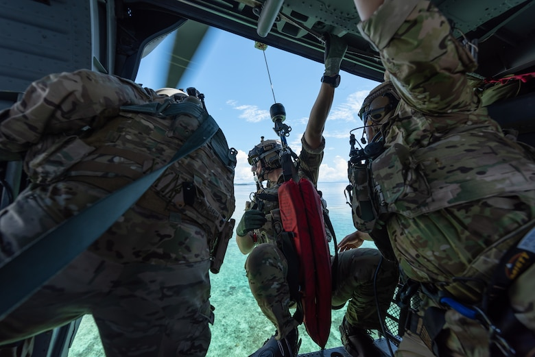 Two U.S. Air Force pararescuemen assigned to the 31st Rescue Squadron, prepare a hoist for a water operation while aboard an HH-60G Pave Hawk, July 26, 2019, out of Kadena Air Base, Japan. Members of the 33rd and 31st Rescue Squadrons from Kadena AB train and work together to provide support for combat rescue and disaster relief. (U.S. Air Force photo by Airman 1st Class Matthew Seefeldt)