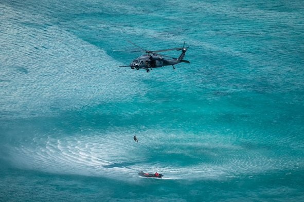 An HH-60G Pave Hawk from the 33rd Rescue Squadron, lowers a pararescuemen into a boat in the ocean during a water operation, July 26, 2019, out of Kadena Air Base, Japan. Members of the 33rd and 31st Rescue Squadrons from Kadena AB train and work together to provide support for combat rescue and disaster relief. (U.S. Air Force photo by Airman 1st Class Matthew Seefeldt)