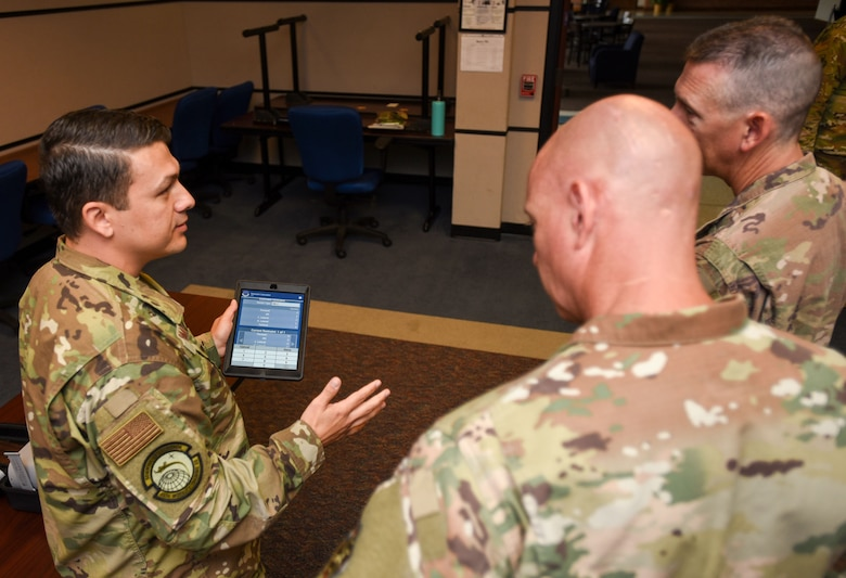 U.S. Air Force Tech. Sgt. Luis Gomez-Duque, 423rd Mobility Training Squadron C-17 Globemaster III apex course director, showcases an app with checklists and guidelines to U.S. Air Force Chief Master Sgt. Chris Simpson, 18th Air Force command chief and U.S. Air Force Chief Master Sgt. Brian Eastman, 305th AMW command chief, during a tour on Joint Base McGuire-Dix-Lakehurst, N.J., Aug. 2, 2019. The app provides information to students and offer a simulation they can use through virtual reality to grasp a better understanding of how it feels to fly an aircraft without physically doing so. (U.S. Air Force photo by Airman 1st Class Ariel Owings)