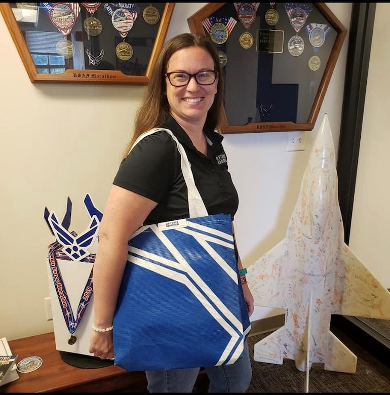 "Rachael McKinney, Air Force Marathon events coordinator and Green Program lead, models the tote bag that will be given away to the ""Fly Fight Win"" challenge participants. The bag was made from sections of a former finish line chute at a previous race. (Courtesy photo)"