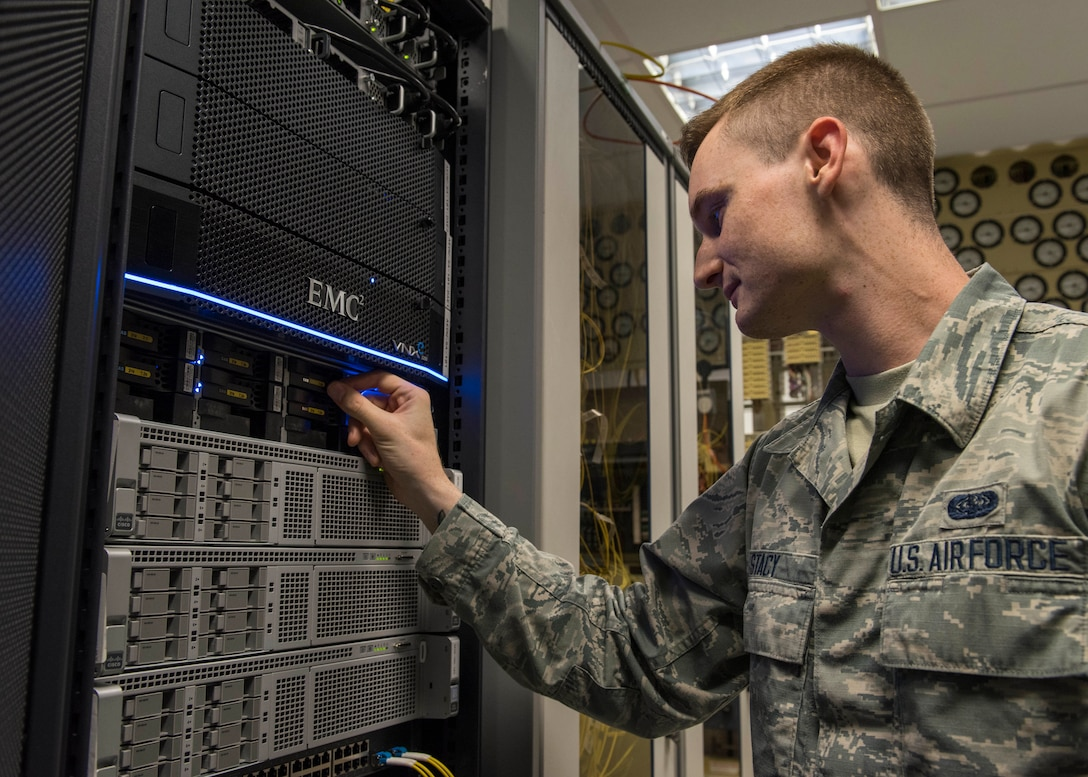 U.S. Air Force Senior Airman Dorian Stacy, 423rd Communications Squadron network operations technician, inspects the backup hard drives at RAF Alconbury, England, August 8, 2019. Stacy is in charge of securing network operations and ensuring proper access and permissions are in place at RAF Alconbury and RAF Molesworth. (U.S. Air Force photo by Airman 1st Class Jennifer Zima)