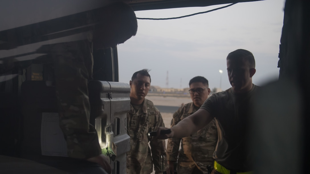 U.S. Army Sgt. Kipp Jones, Staff Sgt. Michael Macho and Sgt. First Class Lai Nguyen with the 8-229th Assault Helicopter Battalion, and U.S. Air Force Staff Sgt. Steven Gentry, 386th Expeditionary Logistics Readiness Squadron, inspect the contents of a U.S. Army UH-60 Black Hawk helicopter at Ali al Salem Air Base, Kuwait, Aug. 9, 2019. Airmen and Soldiers inspect the Black Hawks to ensure they're airworthy to load onto U.S. Air Force C-17 Globemaster III aircraft where they'll undergo transport to a location within the U.S. Central Command area of responsibility. (U.S. Air Force photo by Tech. Sgt. Daniel Martinez)