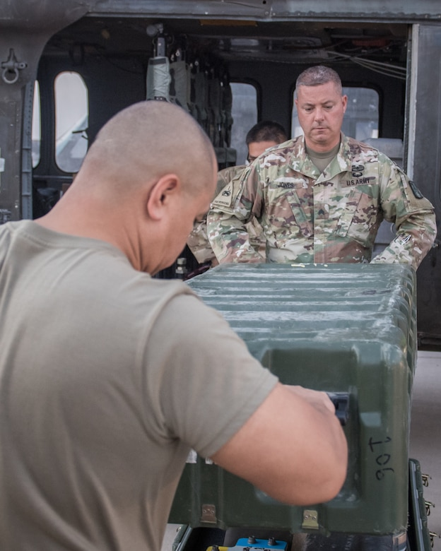 U.S. Air Force Master Sgt. Jesse Cruz, 386th Expeditionary Logistics Readiness Squadron special handling NCO-in-charge, and U.S. Army Sgt. Kipp Jones, 8-229th Assault Helicopter Battalion hazardous materials ground maintenance inspector, remove a storage box for inspection from a U.S. Army UH-60 Black Hawk helicopter at Ali al Salem Air Base, Kuwait, Aug. 9, 2019. A team of Airmen and Soldiers inspected the Black Hawks to ensure they're airworthy to load onto U.S. Air Force C-17 Globemaster III aircraft where they'll undergo transport to a location within the U.S. Central Command area of responsibility. (U.S. Air Force photo by Tech. Sgt. Daniel Martinez)
