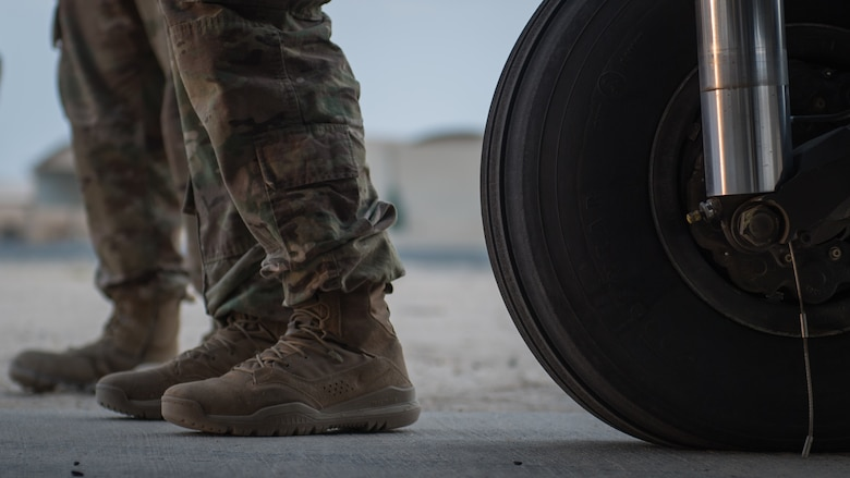 A U.S. Airmen and Soldier stand next to the landing gear of a U.S. Army UH-60 Black Hawk helicopter during a joint inspection of the aircraft at Ali al Salem Air Base, Kuwait, Aug. 9, 2019. Service members assigned to the 386th Expeditionary Logistics Readiness Squadron and the 8-229th Assault Helicopter Battalion inspect the Black Hawks to ensure they're airworthy to load onto U.S. Air Force C-17 Globemaster III aircraft. The Black Hawks will then undergo transport to a location within the U.S. Central Command area of responsibility. (U.S. Air Force photo by Tech. Sgt. Daniel Martinez)