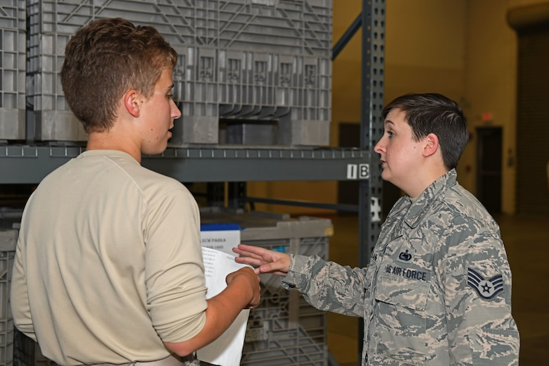two Airmen discuss information in supply