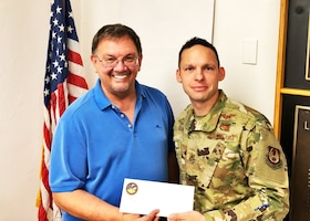 "Edwards Air Force Base Civilian-Military Support Group president Al Hoffman presents a $300 check to Command Chief Master Sgt. Ian EISHEN, the 412th Test Wing Command Chief, at the Lancaster Chamber of Commerce in Lancaster, California, Aug. 8. The donation was made on behalf of local singer, ""Rat Pack"" Ricky Medlin. The money will be used to support the Edwards AFB Youth Center. (U.S. Air Force photo by Danny Bazzell)"