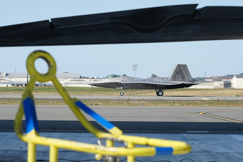 An F-22 Raptor taxis after landing while Airmen assigned to the 673d Logistics Readiness Squadron refuel F-22 Raptors of the 525th Fighter Squadron (the Bulldogs) on Joint Base Elmendorf-Richardson, Alaska, Aug. 9, 2019.  Fuels specialists manage every aspect of the refueling every aircraft on the flight line and are responsible for operating the vehicles, equipment and storage facilities that are essential to refueling operations while ensuring compliance with all safety regulations while handling these volatile liquids.