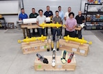 """Lead scientists and engineers from Naval Sea Systems Command Warfare Center Divisions pose for a photo as a representation of a collaborative and innovative effort in development of modular, inexpensive unmanned systems collectively known as the """"microSwarm Family of Systems,"""" or """"µFOS."""