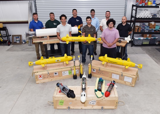 "Lead scientists and engineers from Naval Sea Systems Command Warfare Center Divisions pose for a photo as a representation of a collaborative and innovative effort in development of modular, inexpensive unmanned systems collectively known as the ""microSwarm Family of Systems,"" or ""µFOS."""