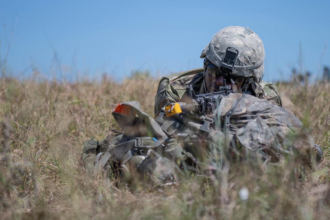 A soldier aims a gun during an exercise.