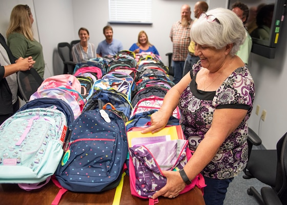 Paula Oliver, administrative assistant at the Naval Surface Warfare Center Panama City Division (NSWC PCD), gathers with other command volunteers to inventory this year's increase in donations for NSWC PCD's annual Back to School Supply Drive.