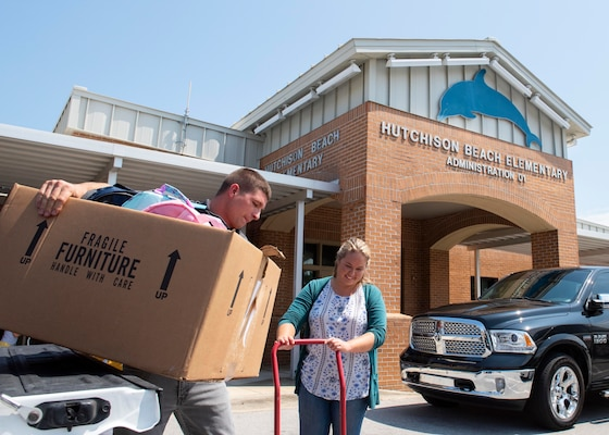 Stephen Carr and Nicole Waters offload donations at Hutchison Beach Elementary School Aug. 8 as part of the Naval Surface Warfare Center Panama City Division's (NSWC PCD) annual Back to School Supply Drive.