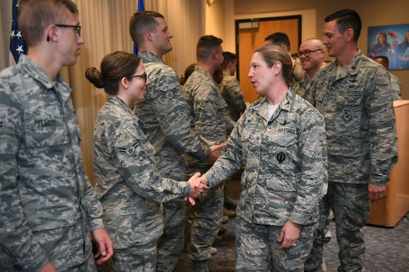 Col. Laurel Walsh, 50th Operations Group commander, congratulates 50th Operations Support Squadron graduates during a ceremony at Schriever Air Force Base, Colorado, Aug. 8, 2019. The 50th OSS is responsible for qualifying both squadron line and staff instructors through a two-week program to establish a baseline of instruction across all mission areas. (U.S. Air Force photo by Katie Calvert)