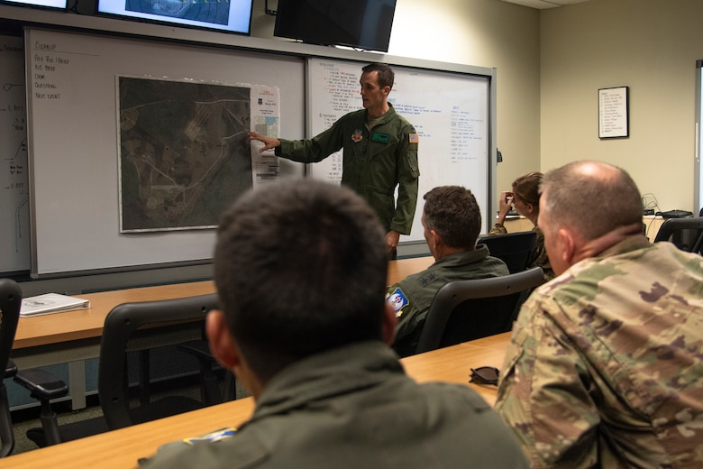 U.S. Air Force Capt. Christopher Allen, 41st Rescue Squadron (RQS) flight commander, briefs Ninth Air Force leadership before a flight at Moody Air Force Base, Ga., Aug. 8, 2019. U.S. Air Force Maj. Gen. Chad Franks, Ninth Air Force commander, flew the initial flight in his flagship aircraft, an HH-60G Pave Hawk assigned to the 41st RQS. Franks, who on separate occasions served as the commander for the 23d Wing and 347th Rescue Group, is a command pilot with more than 3,300 hours in multiple aircraft including HC-130J Combat King II and HH-60G Pave Hawk. (U.S. Air Force photo by Airman 1st Class Taryn Butler)