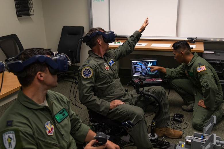 U.S. Air Force Maj. Gen. Chad Franks, center, Ninth Air Force commander, tests the 41st Rescue Squadron's (RQS) virtual reality flight simulator before a flight at Moody Air Force Base, Ga., Aug. 8, 2019. It was Franks' initial flight in the Ninth Air Force commander's flagship aircraft, an HH-60G Pave Hawk assigned to the 41st RQS. Franks, who on separate occasions served as the commander for the 23d Wing and 347th Rescue Group, is a command pilot with more than 3,300 hours in multiple aircraft including HC-130J Combat King II and HH-60G Pave Hawk. (U.S. Air Force photo by Airman 1st Class Taryn Butler)